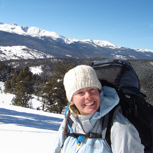 Megan Mueller in winter gear with a hiking pack on in the snowy mountains