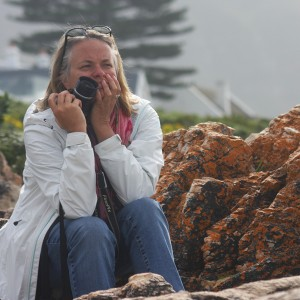 Tehri Parker sitting on a boulder with a camera in hand.